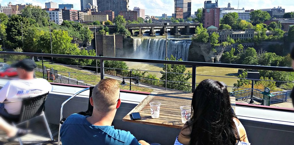 Couple looks from rooftop bar to High Falls, a waterfall in downtown Rochester, NY.