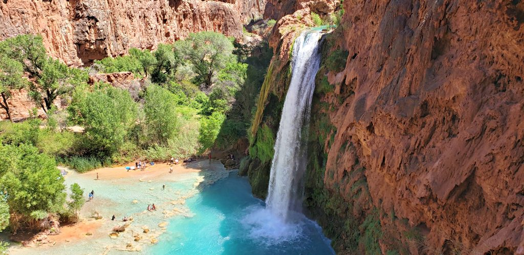 White waters of the tall Havasu Falls plunge down red cliffs and into blue green pools of water.