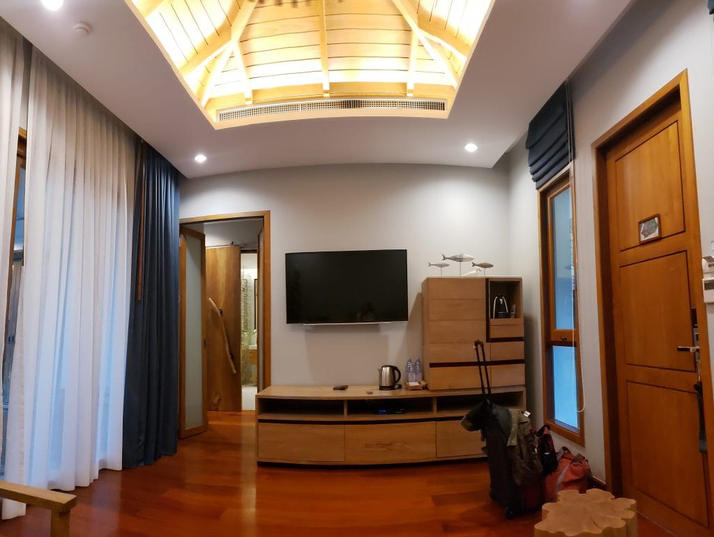 Photo of opposite end of same room with wood shelf, TV, coffee maker and doors to private pool and hall to bath and bedroom. Wooden ceiling alcove.