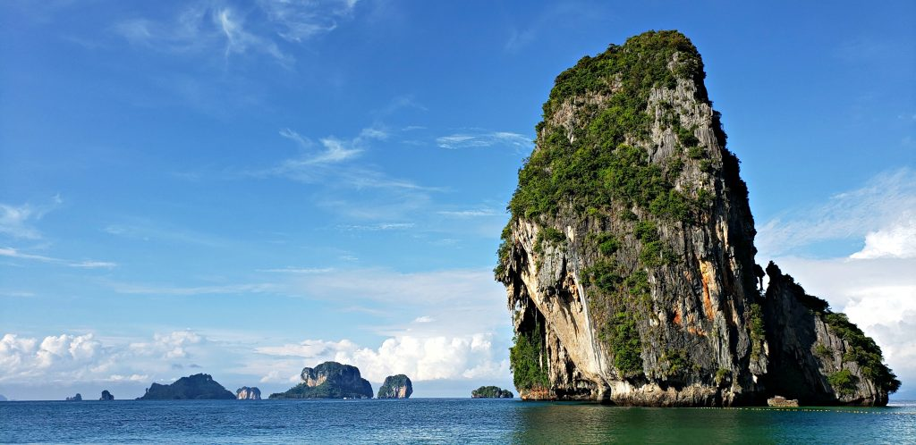 This tall pillar of limestone rock looks more like a sea stack than an island standing high out of green-blue waters. A boat sails in front of the large vertical rock.