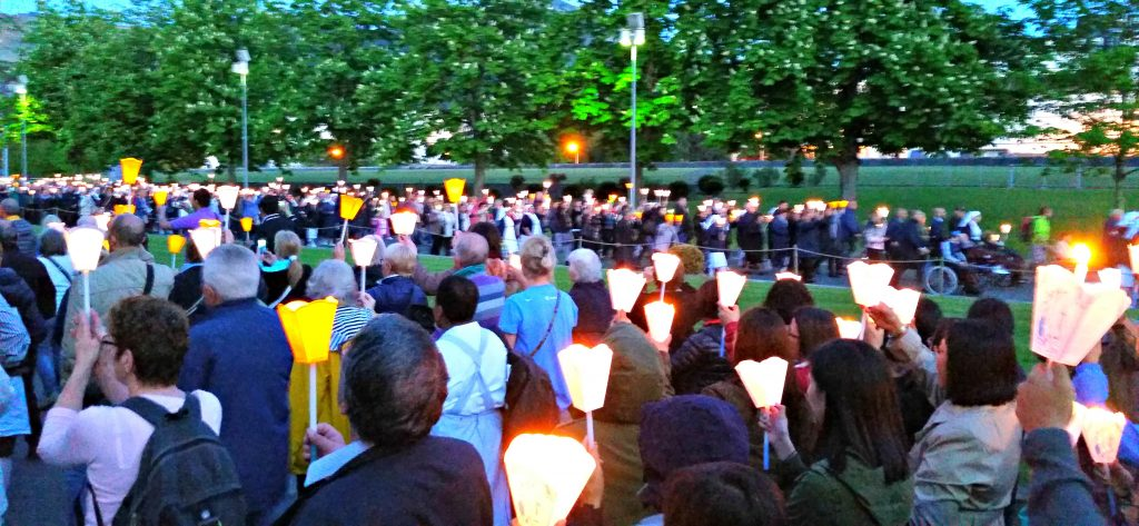 Candlelight processional of people walk along a boulevard in Lourdes, France.