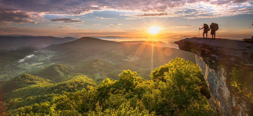 Two backpackers are silouetted by the sunrise as they stand on McAfee's Knob on Appalachian Trail .