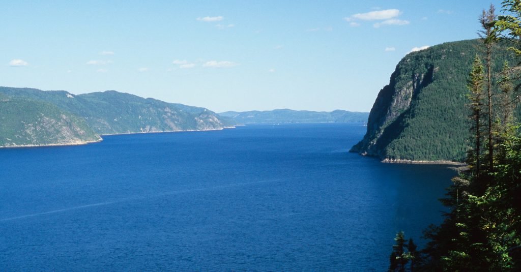 Wide Saguenay Fjord with cliffs rising up to meet the blue skies makes this one of 20 best places to visit in 2020.