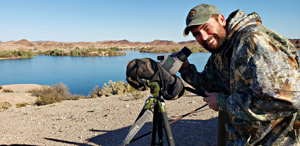 Biologist looks up from scope mounted on tripod, Ducks on water in background during Yuma Bird, Nature & History Festival