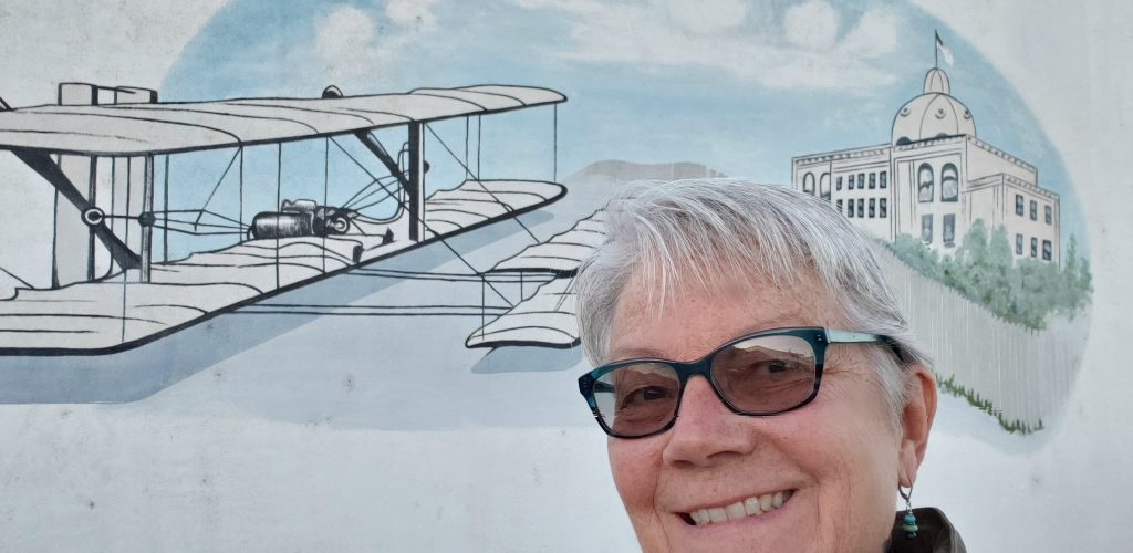 Travel writer Unstoppable Stacey stands in front of wall mural of biplane during Yuma Bird Nature and History Festival