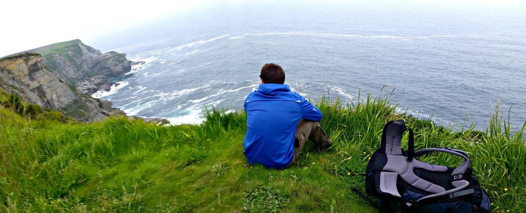 Young man in blue wind coat sits on green grass on edge of cliff overlooking the crashing sea below. It depicts the New Year's resolutions for the Traveler: take time to wonder.