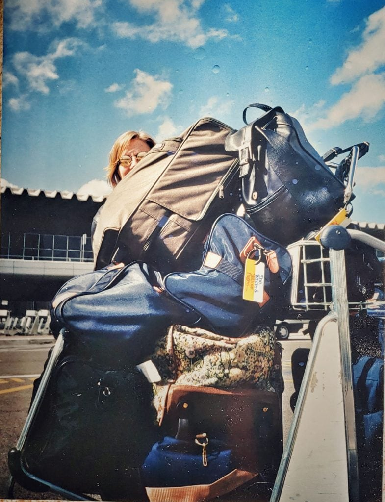 Vintage photo of author peeking from behind a huge pile of suitcases, handbags and wardrobe bags. She looks embarrassed at the Rome airport.
