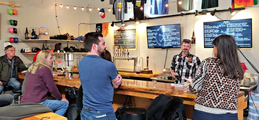 Customers sit around bar in warehouse area while a smiling Nathan Friedman, owner of the Flagstaff brewery, pours