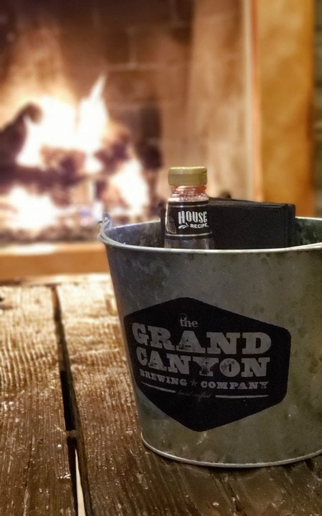 "Galvinized bucket of condiments is imprinted with ""Grand CAnyon Brewing Company - on rough wood table - fireplace blazes in the background."