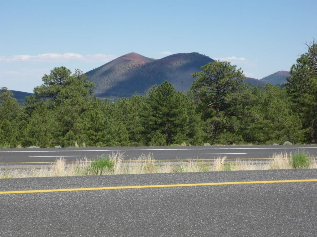 Dark cinder mountain has orange cinders near its rounded peaks