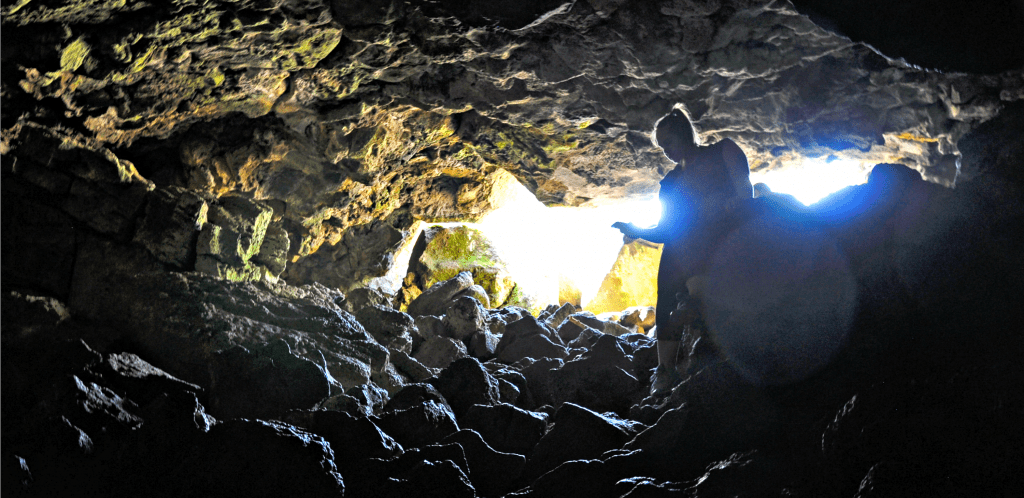 Looking from the dark cave towards the light at it opening. Hiker picks way over rocky floor of cave while descending