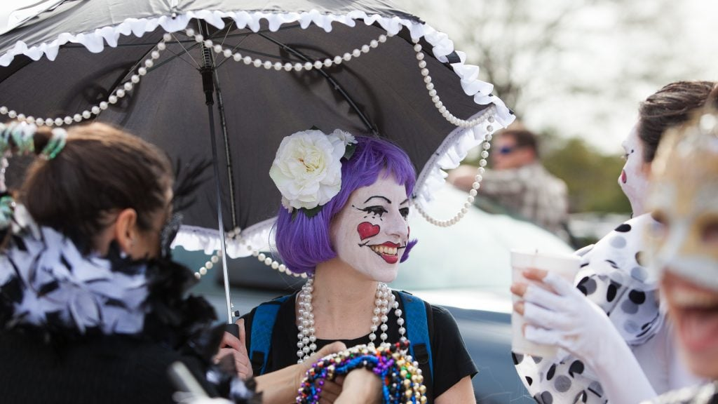 Cute woman with face painted white and smiling red lips under clownish umbrella is kid-friendly Mardi Gras, not scary