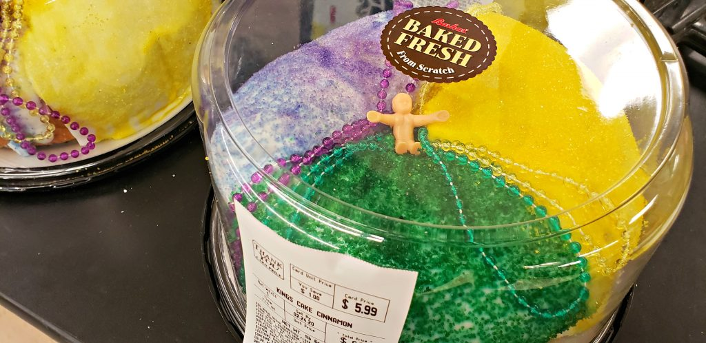 Small plastic baby sits on top of frosted cake with arms outstretched. The baby Jesus is traditionally baked inside the cake for a fun kid-friendly Mardi Gras tradition