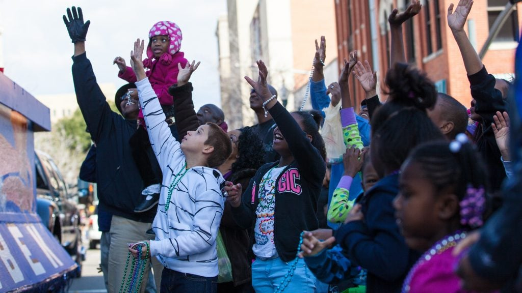 """Kids on the ground and kids on parents shoulders reach for """"throws"""" during Mardi Gras for kids"""