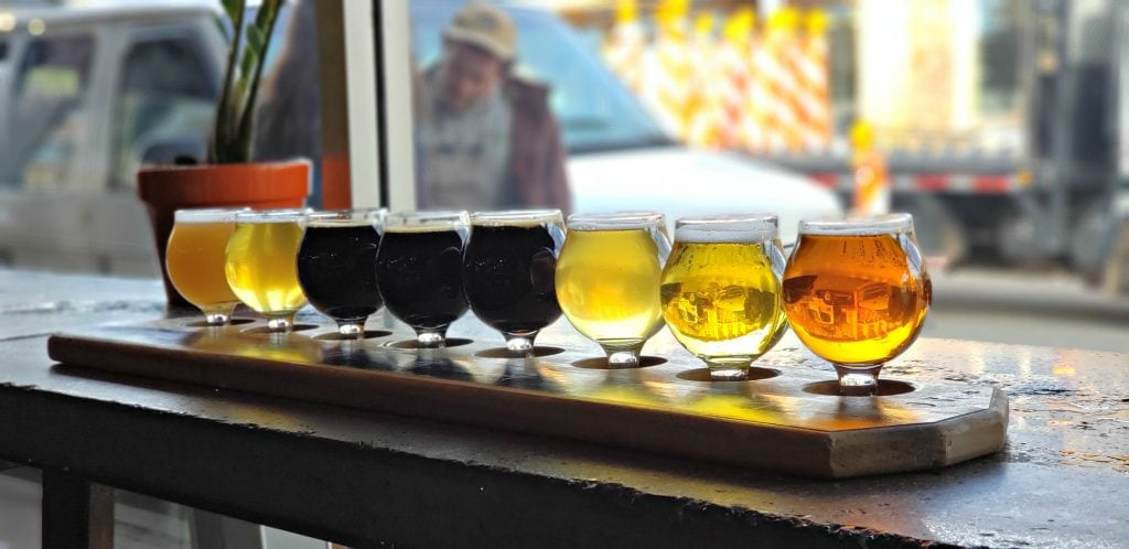 Flight of eight Flagstaff craft beers are in small glasses held in wooden holder. The colors which range from light gold to dark brown and black are back lit by the window where you can see the Flagstaff street