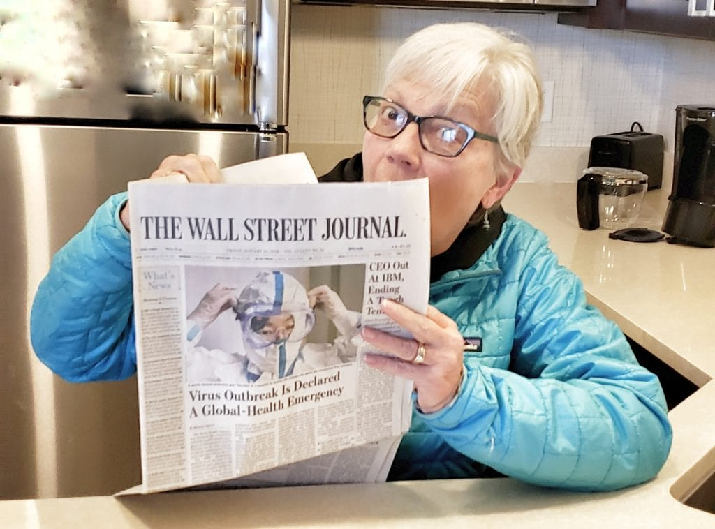 Author looks over edge of Wall Street Journal with large photo of Wuhan Coronavirusworker putting on Hazmat suit