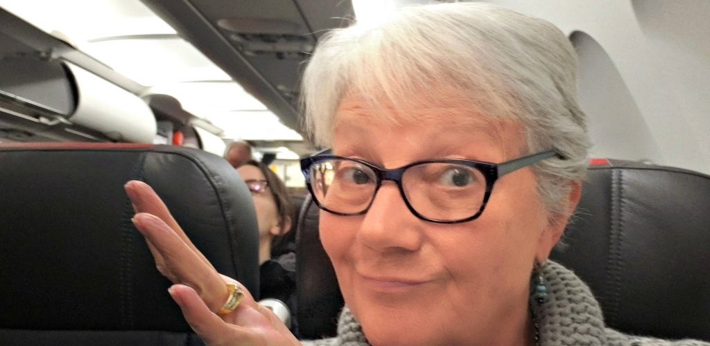 """Unstoppable Stacey sits in airplane seat with hand in air as is signaling """"I'm not sure if I need a mask for Wuhan Coronavirus protection."""""""