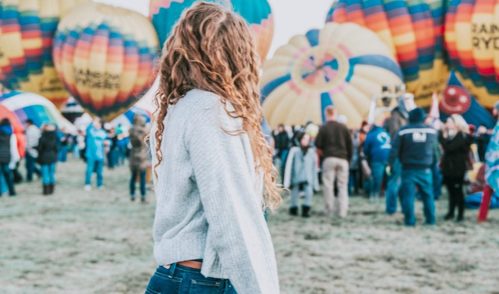 Young woman stands in front of hot air balloons ready to lift off at Albuquerque Balloon Festival - Albuquerque guide
