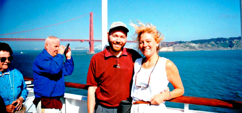 Dan and Stacey Wittig pose for a photo next to cruise ship railing with the Golden Gate Bridge in the background
