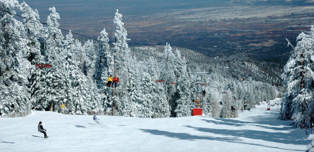 Looking down at ski runs and trees covered in snow. Skier is on his way down. The City of Albuquerque is seen - snowless - below