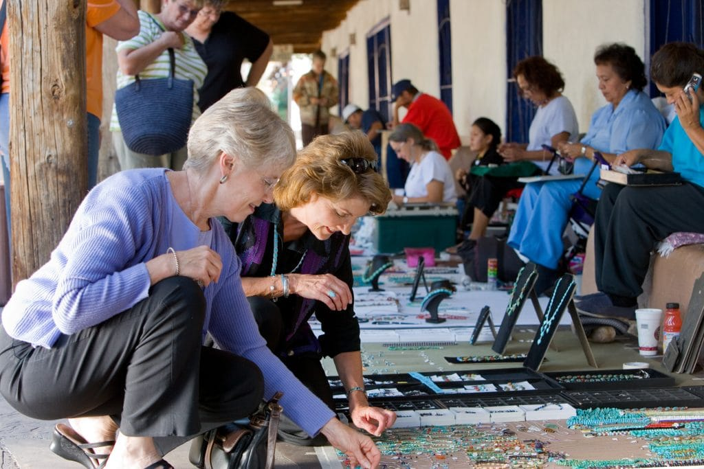 Two middle aged women squat down on Albuquerque sidewalk to view jewelry made by Native artisans