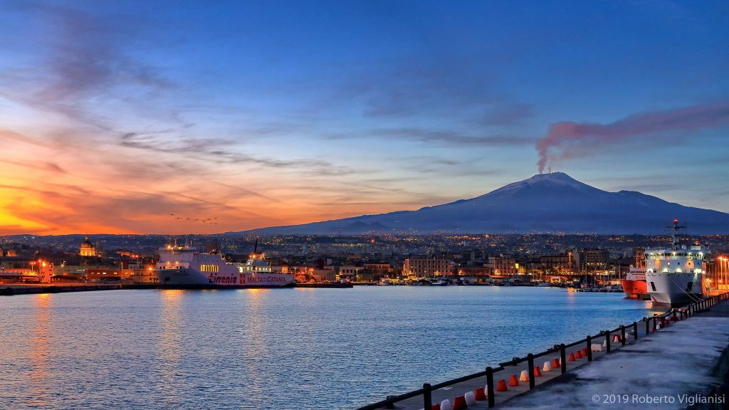 Harbor at sunset with silhouette of Mount Etna volcano steaming in the background