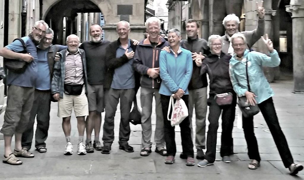 11 smiling people laugh in the Medieval neighborhood of Santiago after finishing The Way