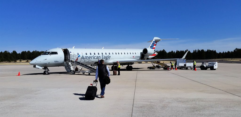 small communter jet sits on Flagstaff travel runway while passenger walks on tarmac with carry on bag - clear skies overhead, trees on other side of runway at airport in Flagstaff Arizona