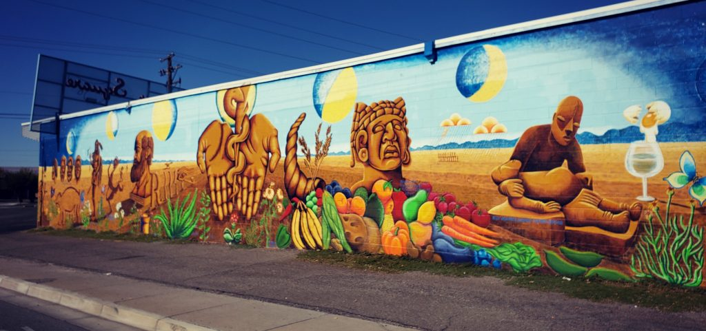 Mural on side of one story long building. Mural depicts medical practices of ancient people