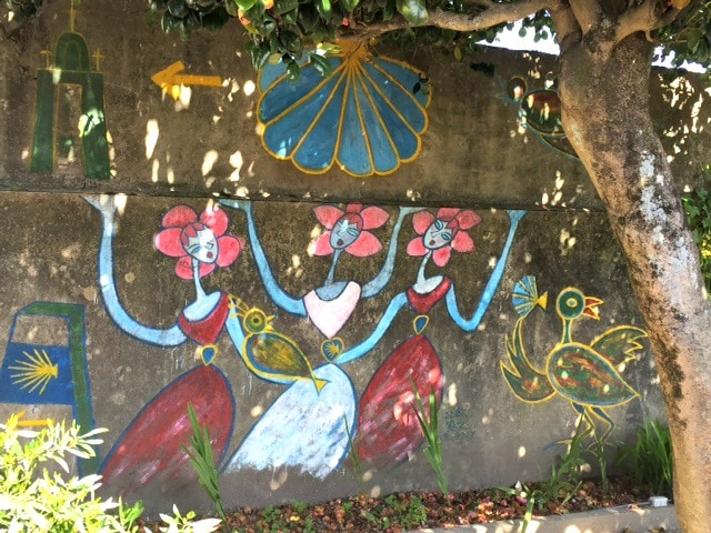 a mural of dancing abstract ladies with skirts, flowers and the Shell of St James. how Coronavirus affects travel