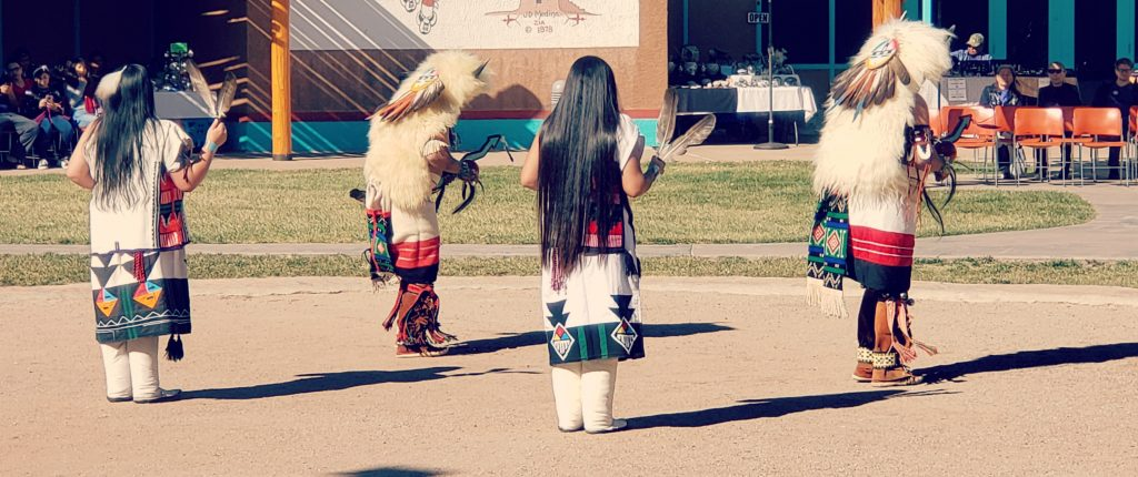 4 people of Zuni dance in traditional regalia in the sandy dance circle at Indian Pueblo Cultural Center one of the best things to do in Albuquerque New Mexico.