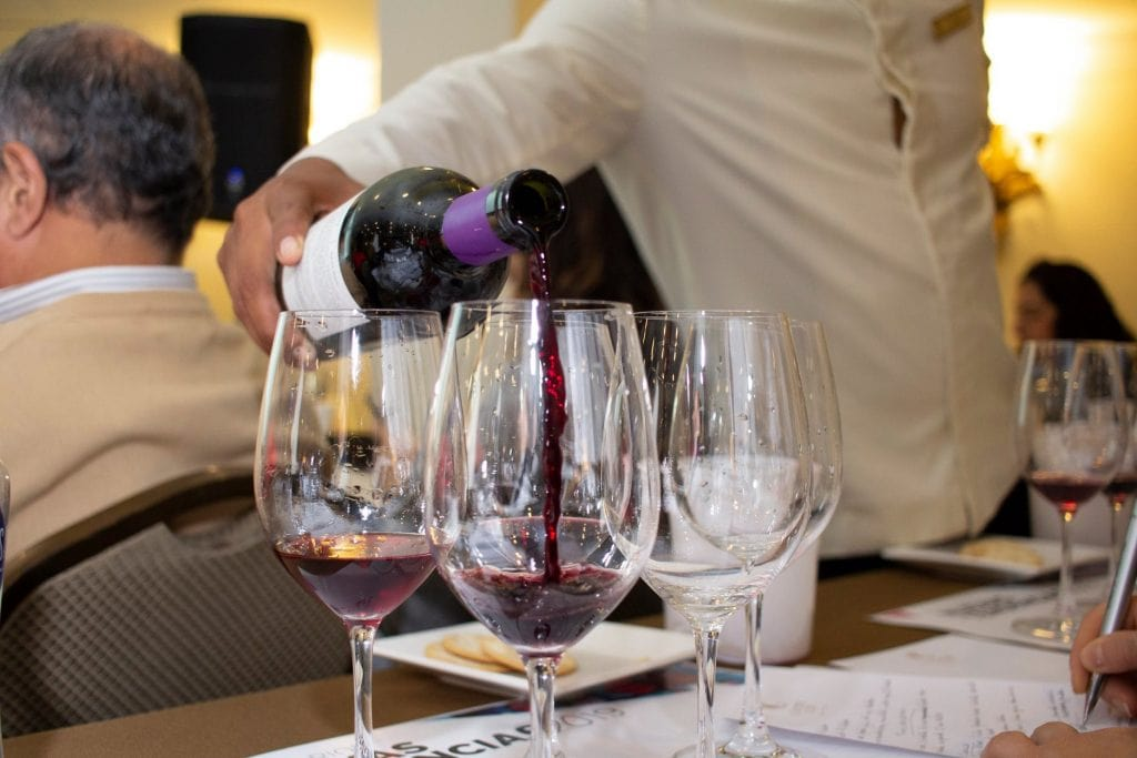 Server pours inky dark wine into three wine glasses for World Malbec Day