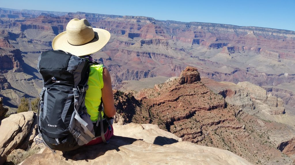 Arizona travel writer Stacey Wittig sits near Kaibab Trail with her back to the camera. She wears backpack and wide-brimmed cowboy hat
