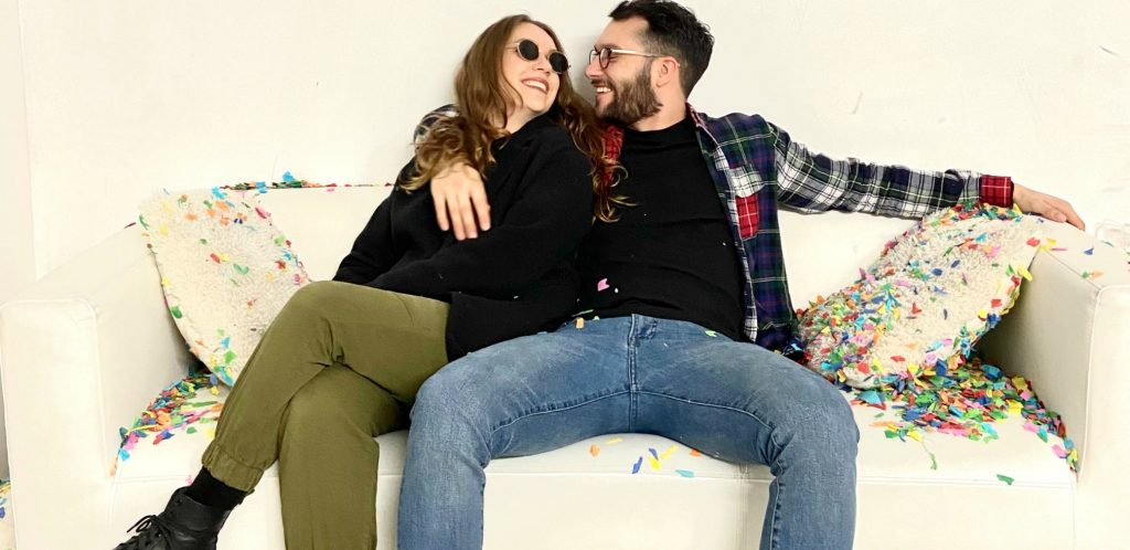 Happy young couple stretch out on couch at home