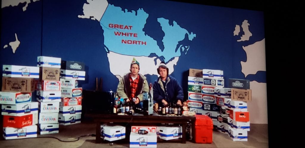 """Bob and Doug McKenzie, a pair of fictional Canadian brothers host """"Great White North"""", with giant map of North America behind them"""