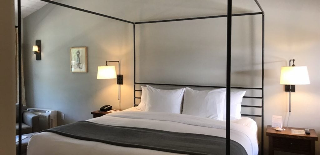 Modern, wrought iron 4-posted bed with luxury bedding