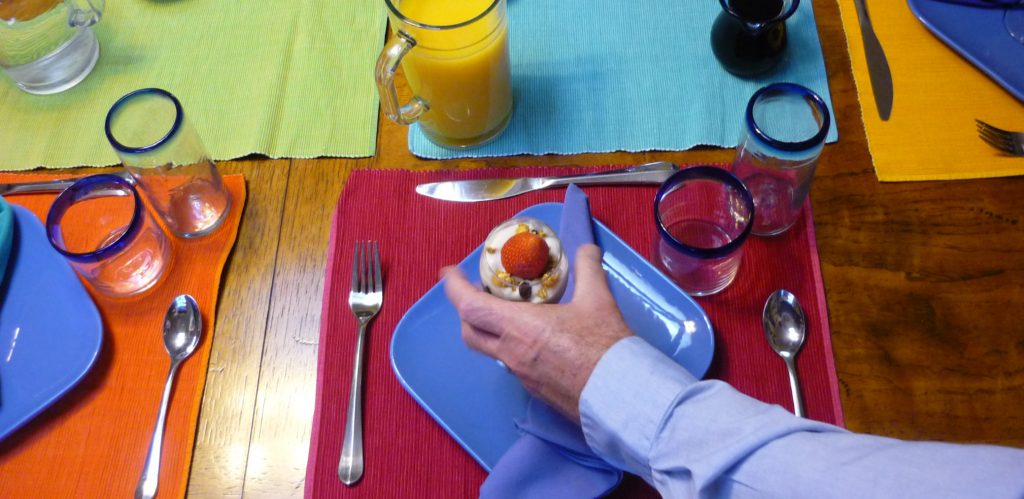 Server's hand reaches onto brightly decorated table with a fruit parfait