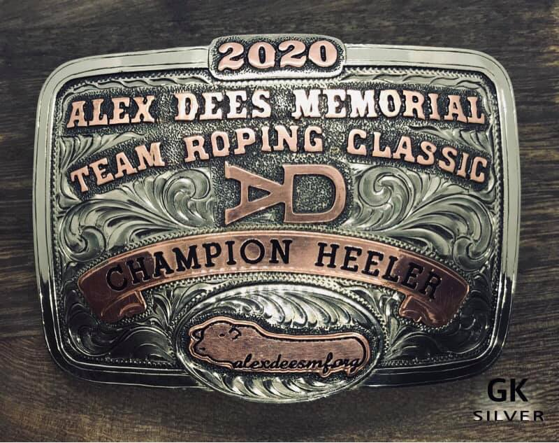 "Close up image of handmade belt buckle which reads: ""Alex Dees Memorial Team Roping Classic Champion Heeler"""