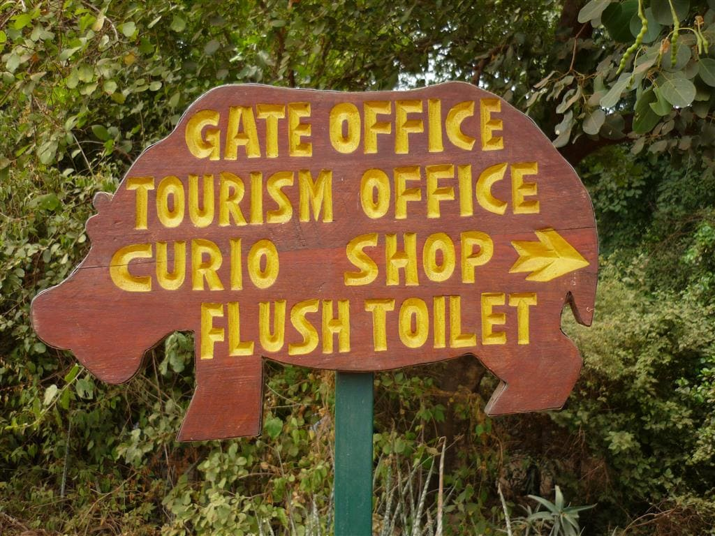 "wooden sign cut in the shape of a hippo says ""Gate Office, Tourism Office, Curio shop and Flush Toilet at Manyara wildlife safari camp park headquarters"