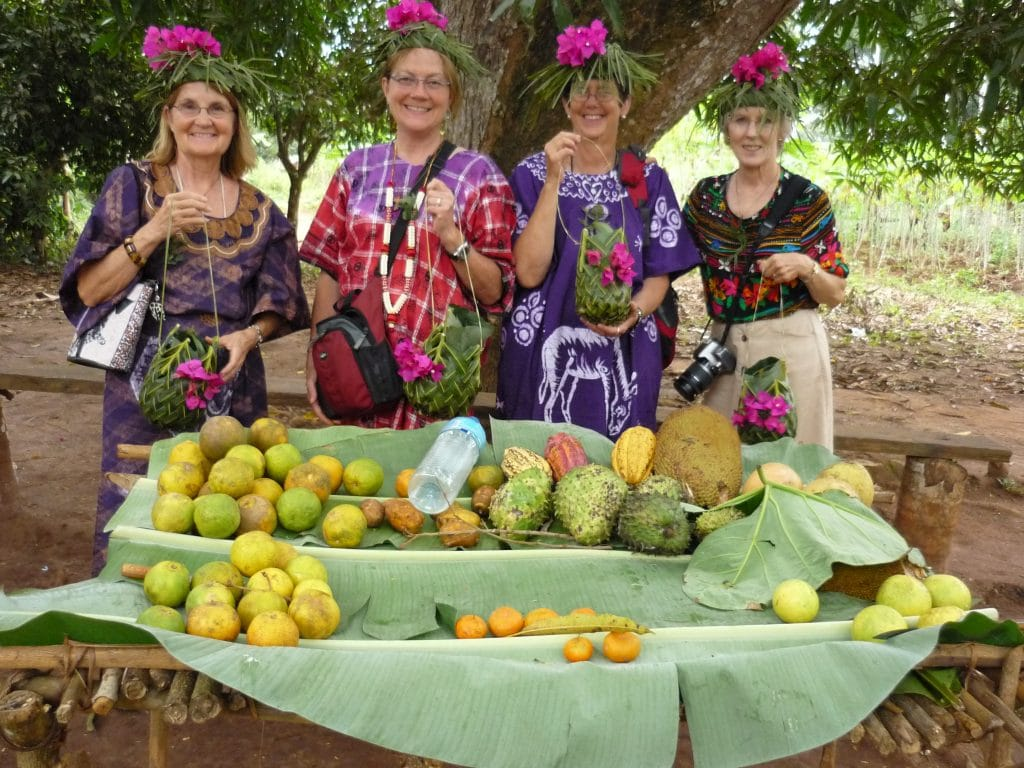 Author stands with three other women dressed in local garb behind table laden with rare exotic fruits