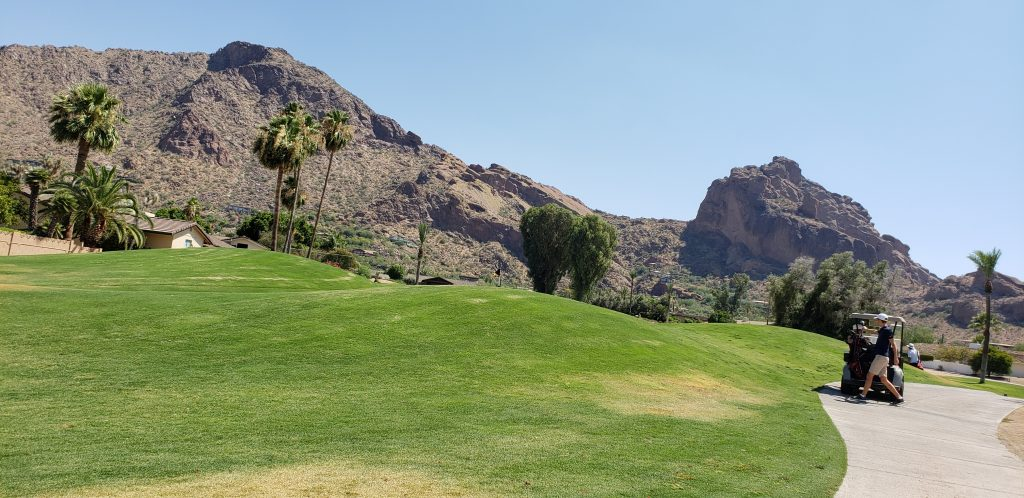 Golf cart on concrete path that weaves past a long green toward the reddish, pyramid-shape mountain in the background of the green golf course at Mountain Shadows golf course