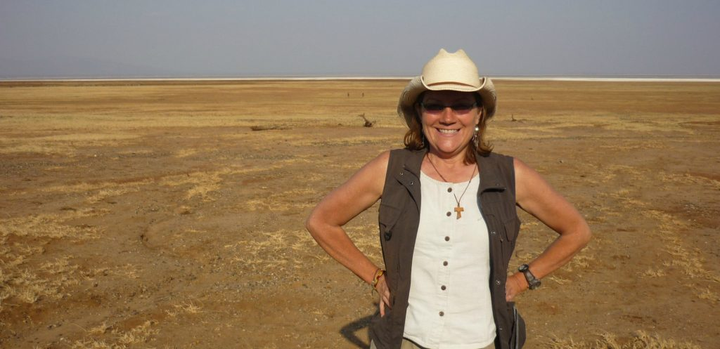 Arizona travel writer Stacey Wittig stands with hands on hips in front of vast grasslands during Lake Manyara NAtional PArk safari - wears starw cowboy hat and safari vest