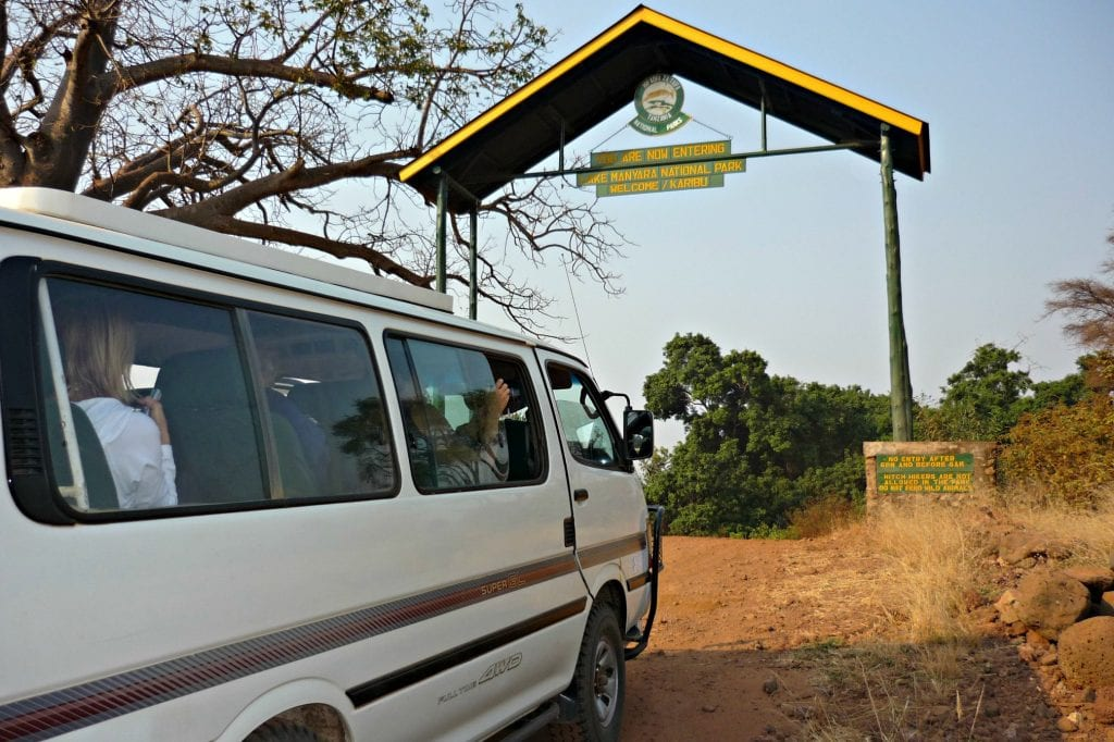 """white safari vehicle with pop-up roof starts through tall, rustic gate with sign reading, """"You are now entering Lake Manyara National Park safari"""""""