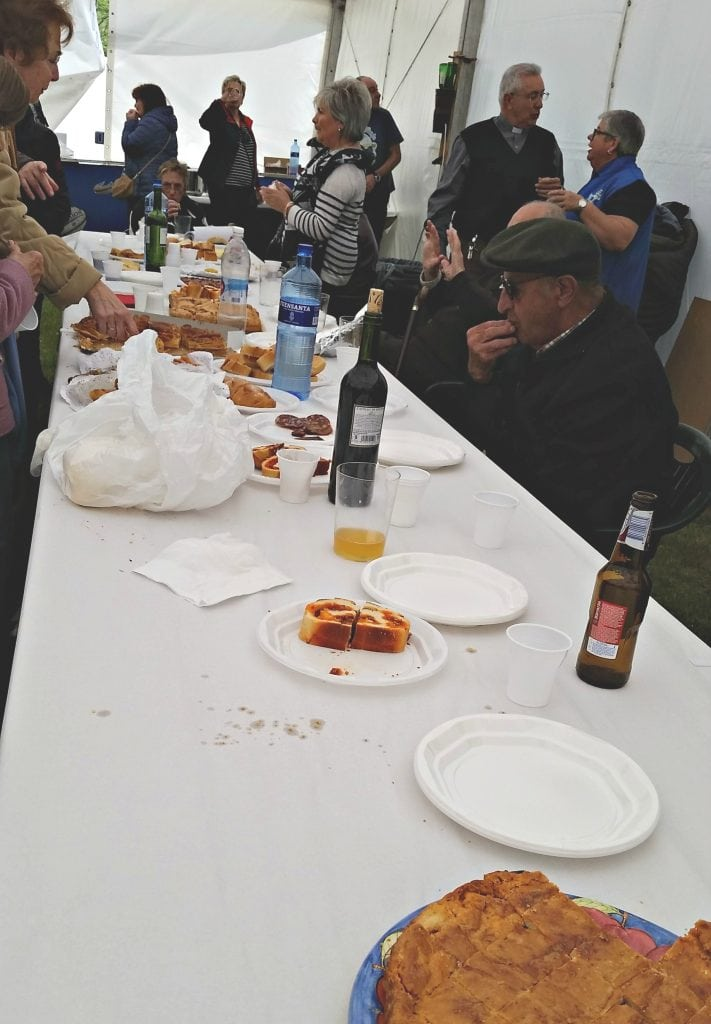 Empty, used plates and plates of Asturian regional food line long table with white plastic tablecloth, people socialize on the backside of the table near the white tent wallsfood
