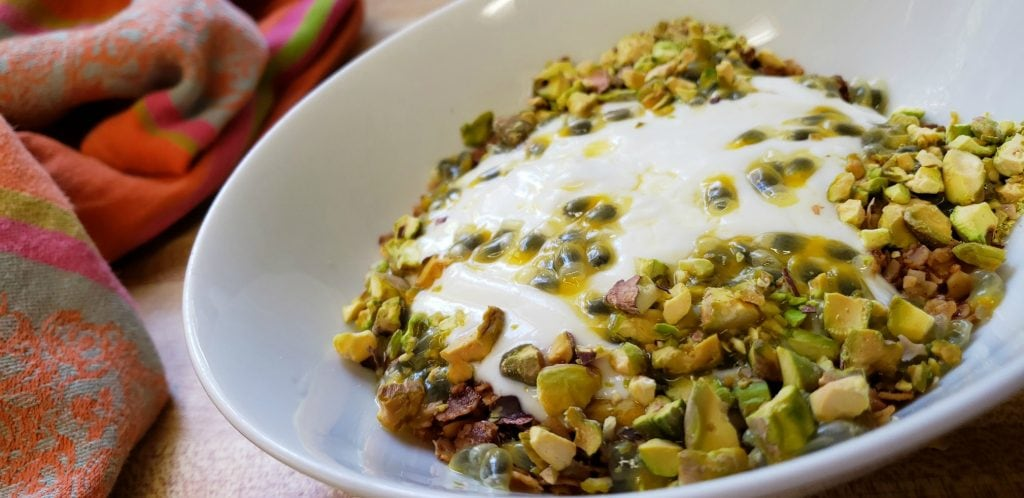 white bowl filled with yogurt, dribbled with green passion fruit seeds and juice, sprinckled with chopped pistachios