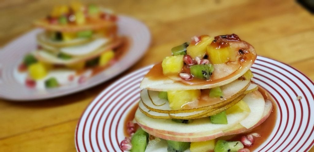 thinly sliced fruit stacked with cubed pineapple and kiwi separating slices pooled in passionfruit sauce
