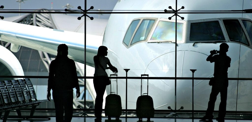 silouetted of woman traveler with best carry on for a woman as she looks at huge airplane at airport. best lightweight luggage for international traveling