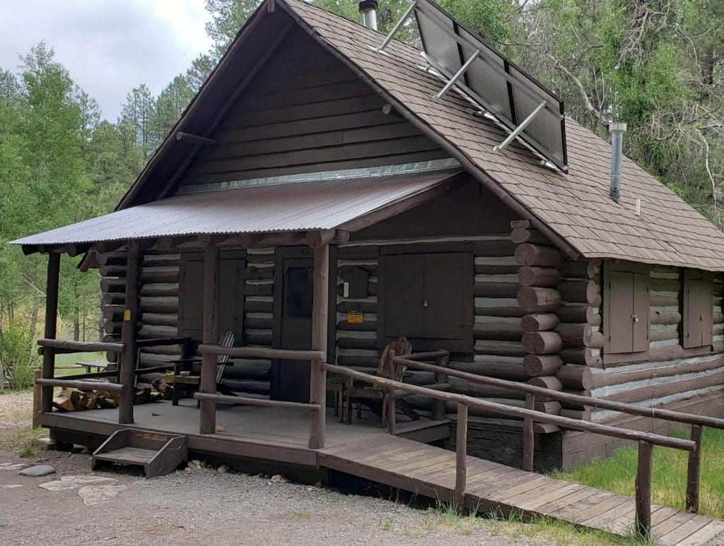 Cabins in Flagstaff include this historic log cabin with plaster chinking between the logs. The green of the Ponderosa pine tress is behind the Flagstaff cabin