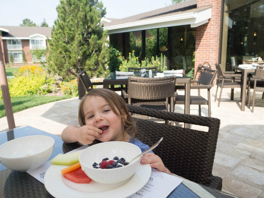 Little girl eats at outdoor patio table with hotel on background showing lodging in Flagstaff