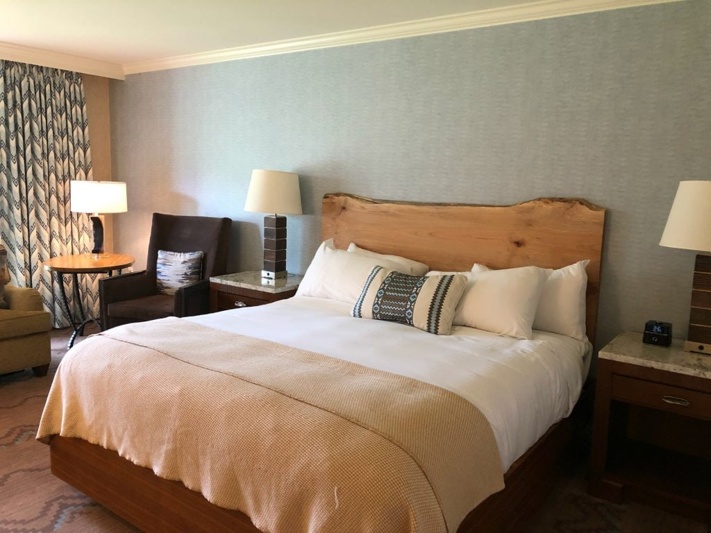 interior of hotel with king bed with organic wood headboard at lodging in Flagstaff